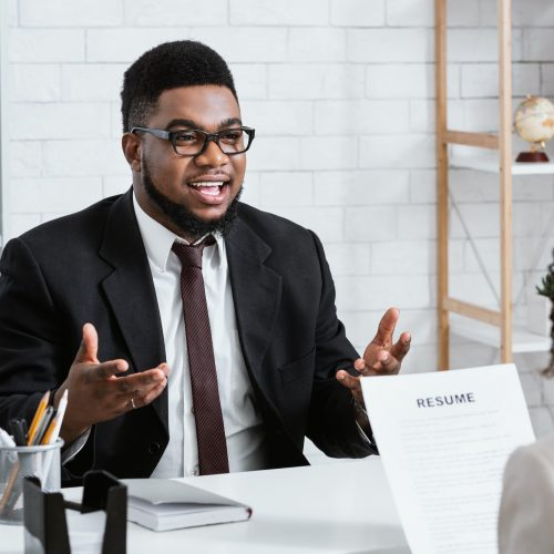 Human resources manager communicating with positive vacancy applicant on employment interview at